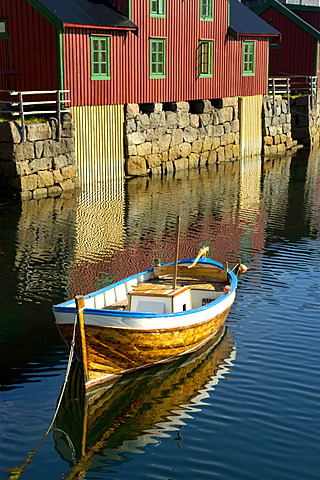 Colourful Rorbuer houses at the shore with boat Stamsund Vestvagoya Lofoten Norway