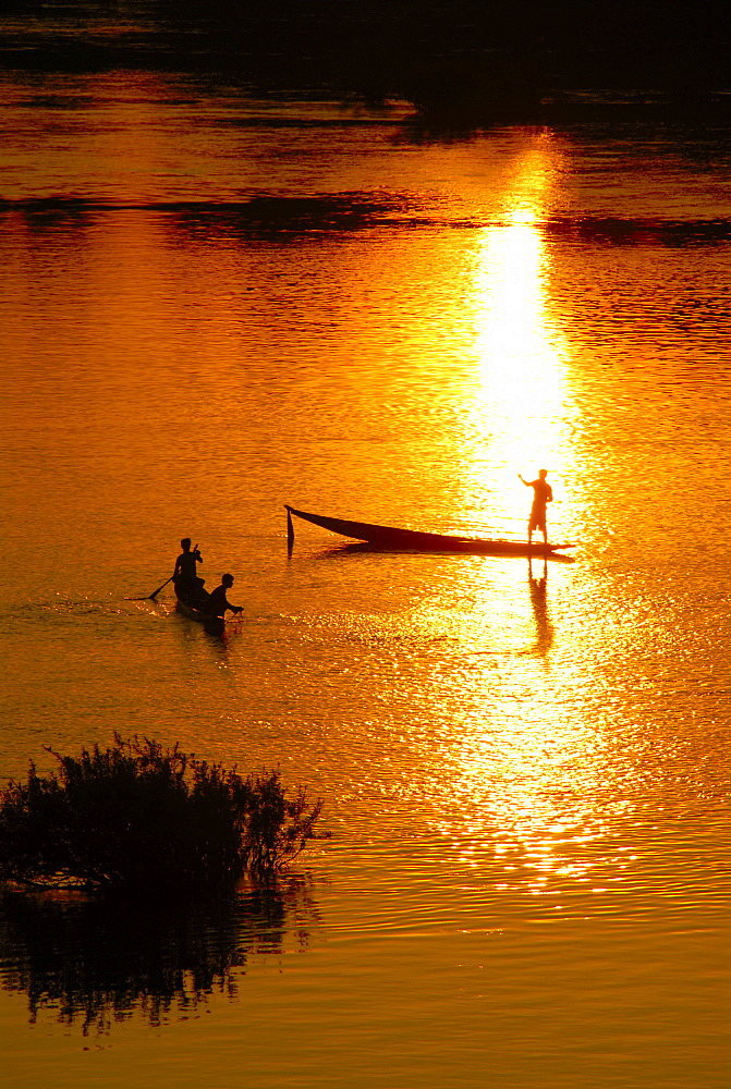 Sunset fishermen in boats on the Mekong River Muang Khong Si Phan Don Laos