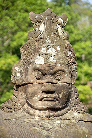 Portrait face of a Khmer stone figure at South Gate Angkor Thom Siem Reap Cambodia