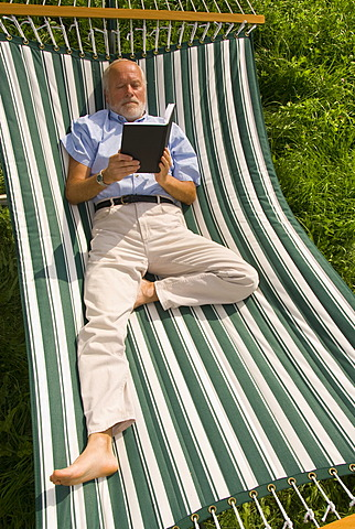Elderly gentleman lying in a hammock reading a book