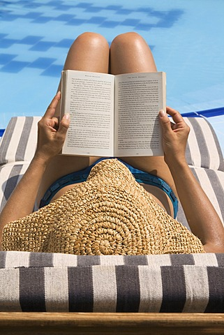 Woman reading by swimming pool