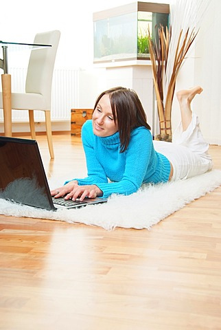 Woman on sheepskin rug using laptop at home