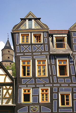 German Framework Road. Ancient framework-house at the marketplace, in background the witch-tower, landmark of the town Idstein, Hesse, Germany