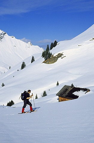 Woman snowshoeing near a mountain hut in the valley Kleinwalser Austria