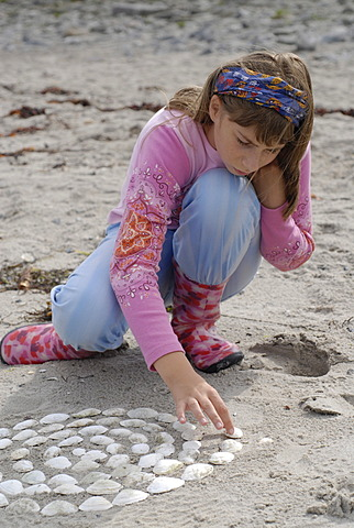 Girl puts with shells mandalas