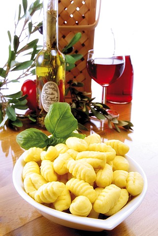 Italian ambiance: gnocchi with basil, red wine, olives and an olive twig