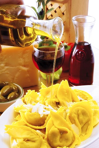 Italian ambiance: drizzling olive oil over an agnolotti dish with parmesan, red wine and olives