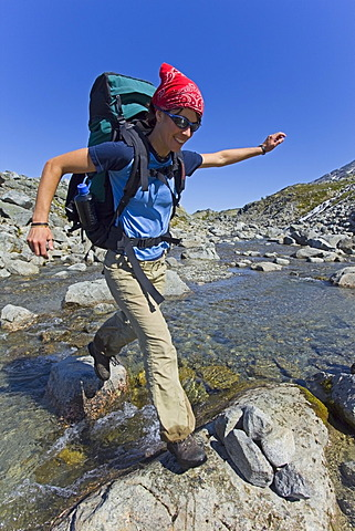 Young woman jumping across a creek, hiking, backpacking, hiker with backpack, historic Chilkoot Trail, Chilkoot Pass, near Crater Lake, alpine tundra, Yukon Territory, British Columbia, B. C., Canada