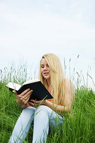 Young blonde woman sitting on a lawn, reading a book