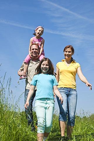 Family walking relaxed in a flower meadow