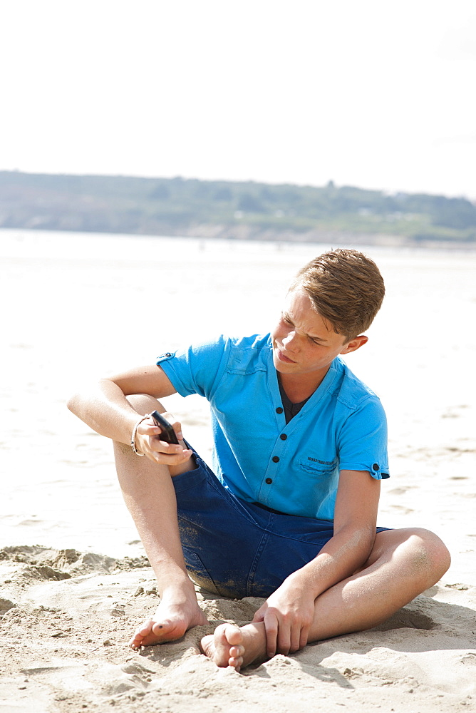 Teenager using his smartphone on a beach