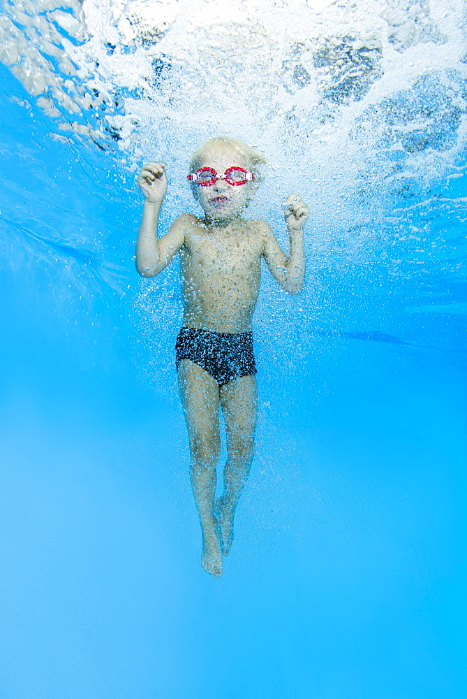 Little boy with swimming goggles, jumping into swimming pool, underwater, Ukraine, Europe - 832-380305