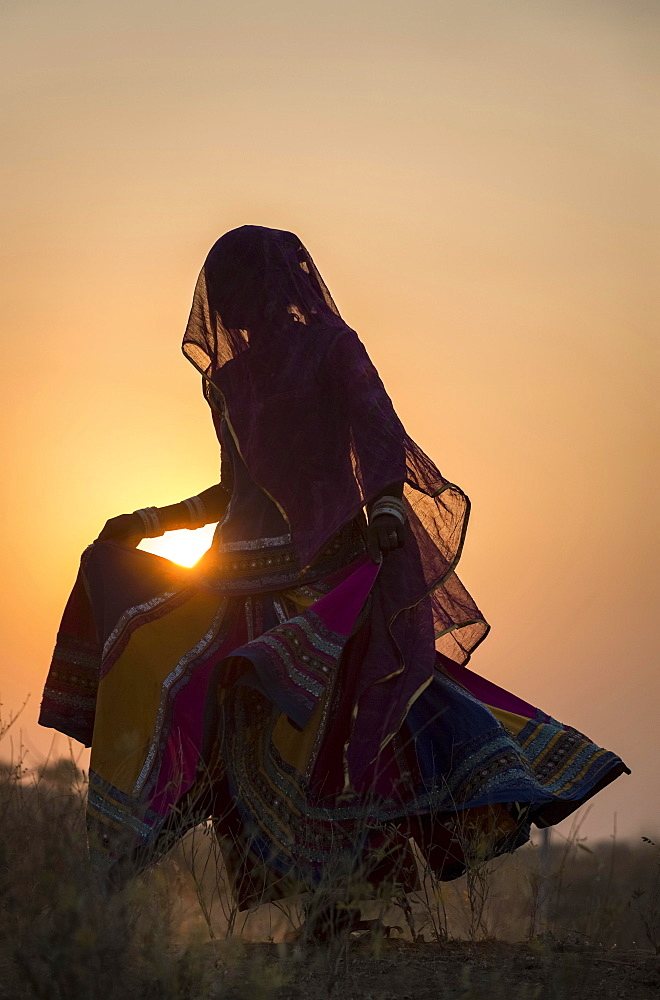 Woman dancing in front of the sun, Pushkar, Rajasthan, India, Asia