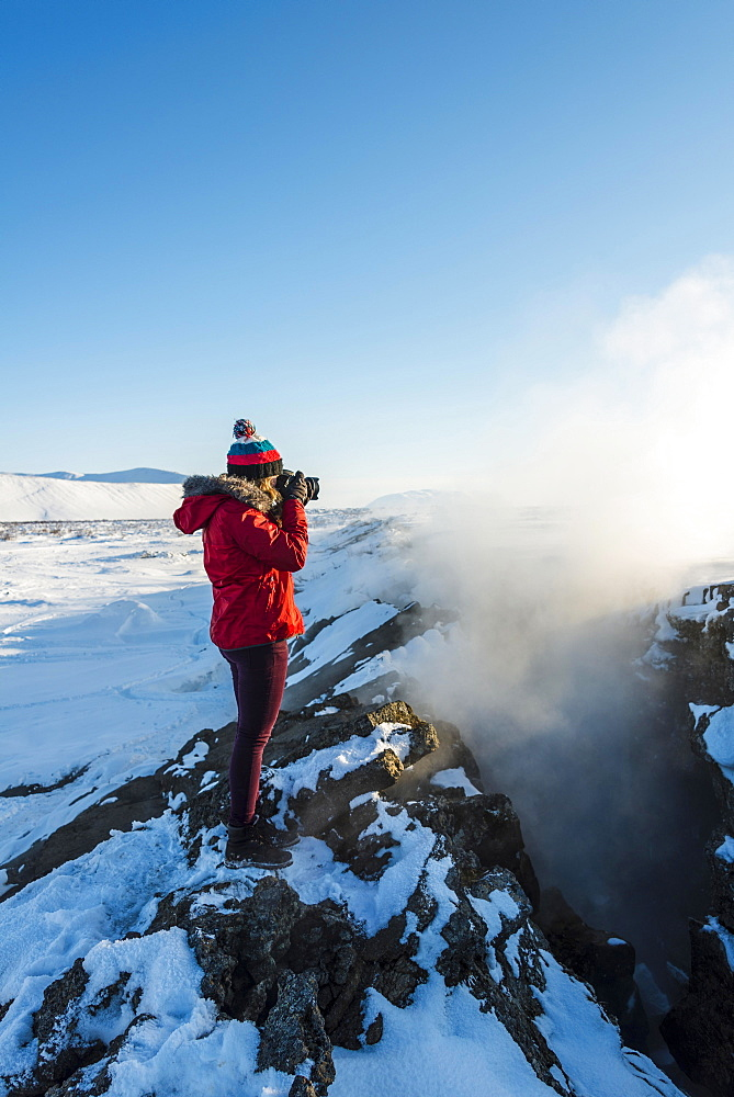 Woman standing at divergent tectonic boundary between North American and Eurasian plates, photographing, Mid-Atlantic Ridge, rift valley, Krafla, Myvatn, Northern Region, Iceland, Europe