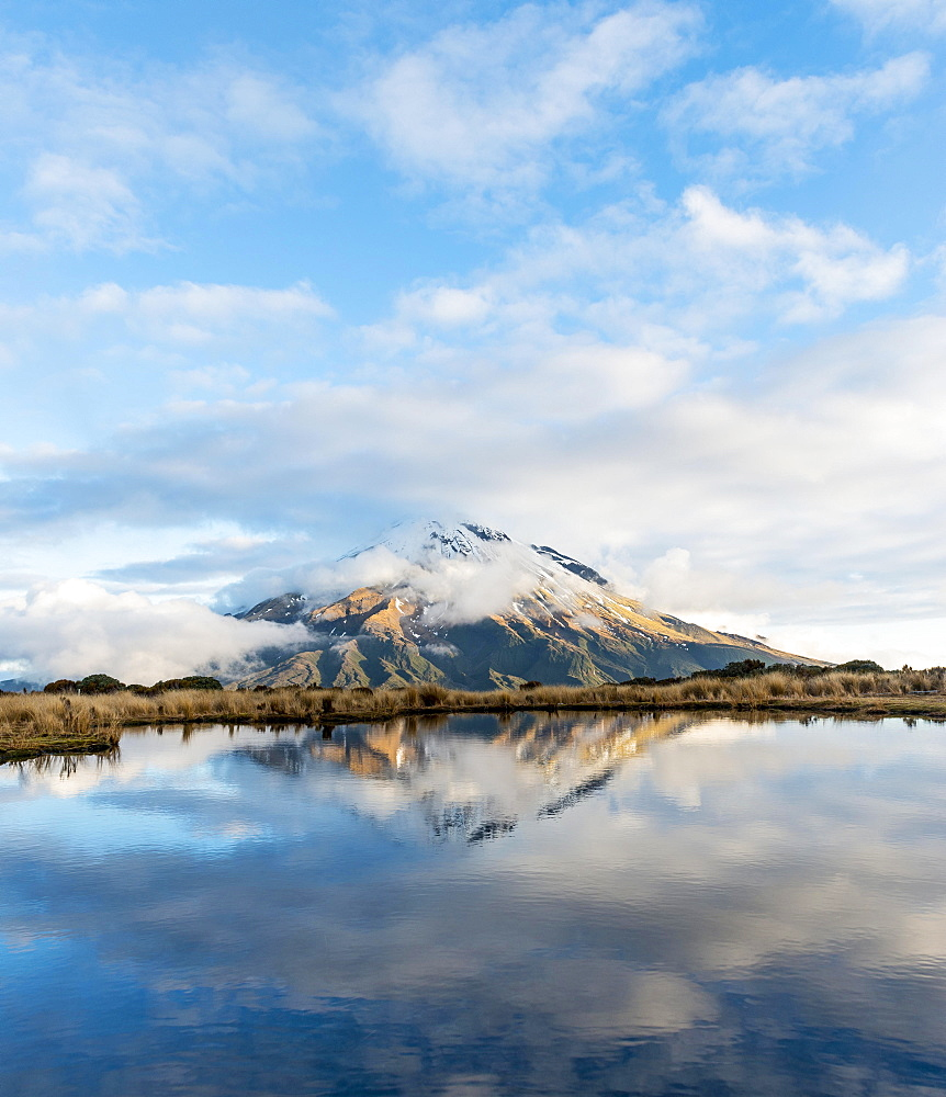 Reflection in Pouakai Tarn, stratovolcano Mount Taranaki or Mount Egmont with cloud, Egmont National Park, Taranaki, New Zealand, Oceania