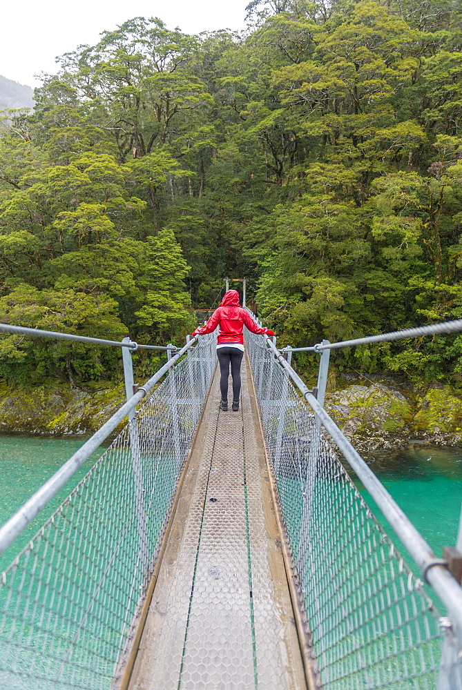 Woman crossing Suspension Bridge, Blue Pools, Haast Pass, West Coast, Southland, New Zealand, Oceania