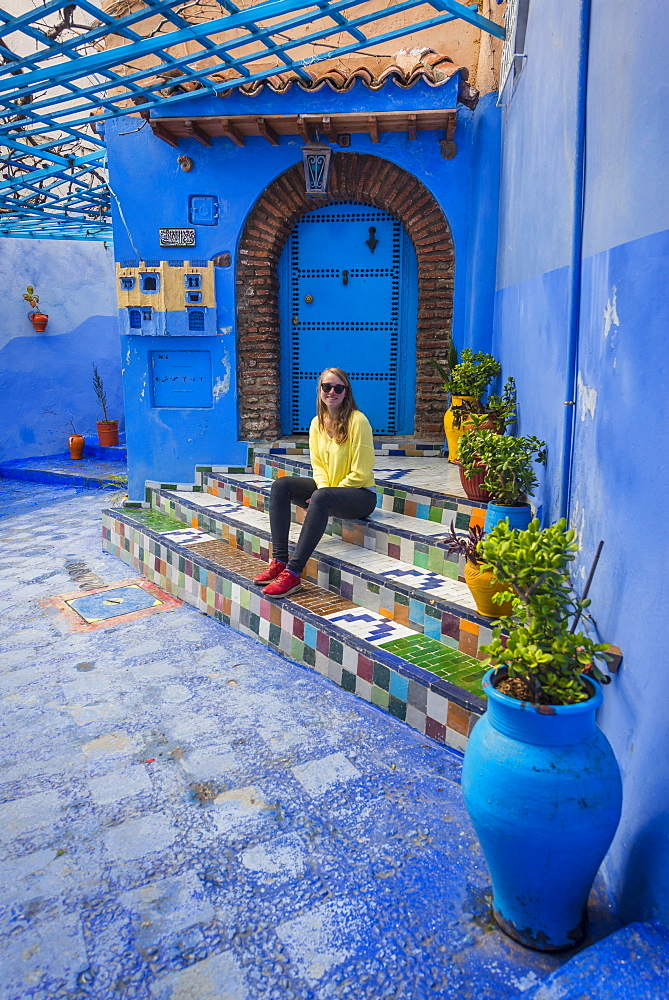 Young woman in the old town sits on a staircase, blue house walls, medina of Chefchaouen, Chaouen, Tangier-Tétouan, Kingdom of Morocco - 832-381324
