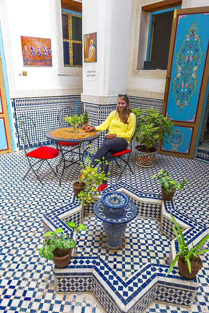 Young woman in a Moroccan courtyard, blue tiles and fountain, Fès-Boulemane, Morocco, Africa