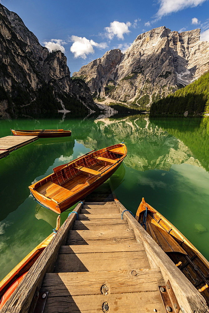 Stairs in mountain lake with boats, Seekogel peak in the back, Lake Prags, Dolomites, Italy, Europe
