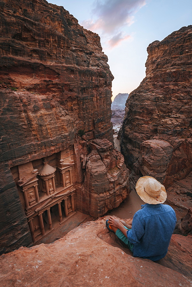 Tourist sits at the edge of a rock and looks from above into the canyon Siq, Pharaoh's treasure house beaten into the rock, facade of the treasure house Al-Khazneh, Khazne Faraun, Mausoleum, Nabataean city Petra, near Wadi Musa, Jordan, Asia