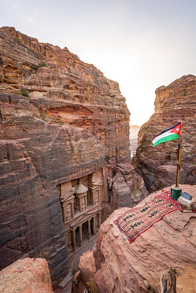 View from above into the gorge Siq, Pharaoh's treasure house carved into rock, facade of the treasure house Al-Khazneh, Khazne Faraun, mausoleum in the Nabataean city Petra with Jordanian flag, near Wadi Musa, Jordan, Asia