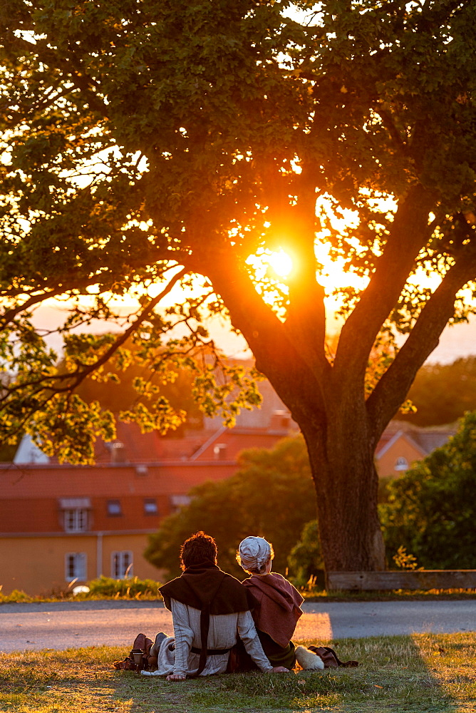 Visitors of the Medieval Week watch sunset over the Old Town, Visby, Gotland Island, Sweden, Europe