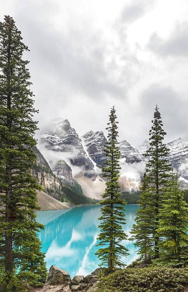 Clouds hanging between the mountain peaks, reflection in turquoise glacial lake, Moraine Lake, Valley of the Ten Peaks, Rocky Mountains, Banff National Park, Alberta Province, Canada, North America
