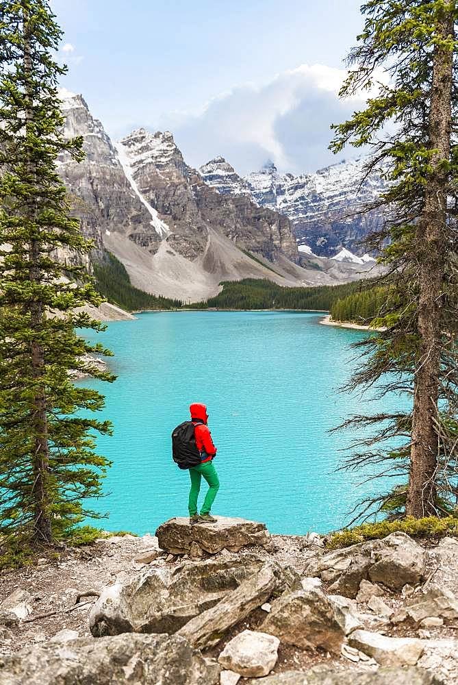 Hiker standing on the shore of a lake, mountain peaks at the back, turquoise glacial lake, Moraine Lake, Valley of the Ten Peaks, Rocky Mountains, Banff National Park, Alberta Province, Canada, North America