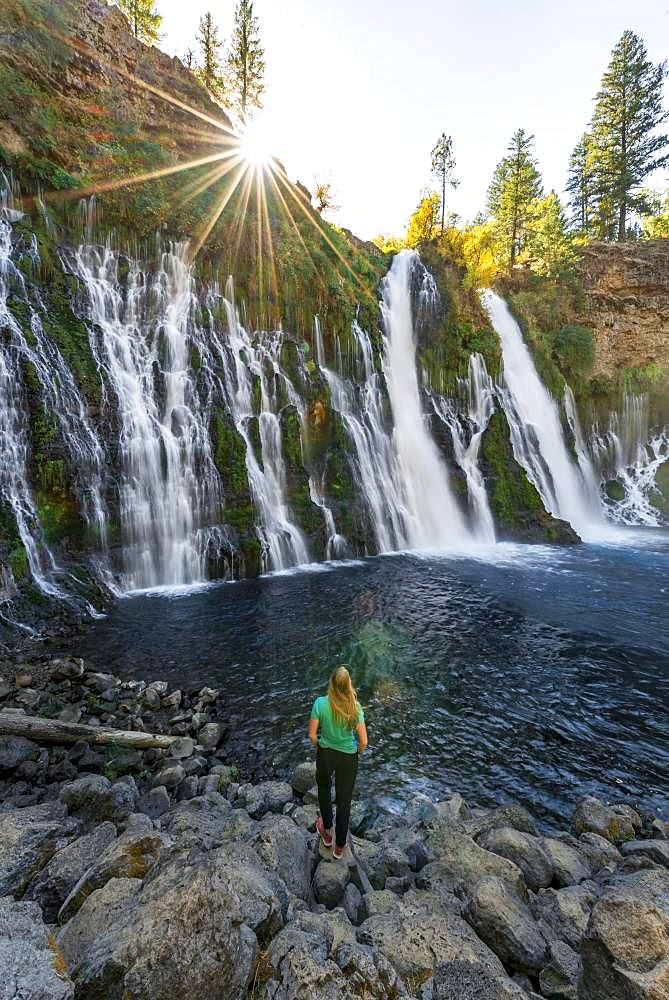 Young woman standing at a waterfall, McArthur-Burney Falls Memorial State Park, California, USA, North America