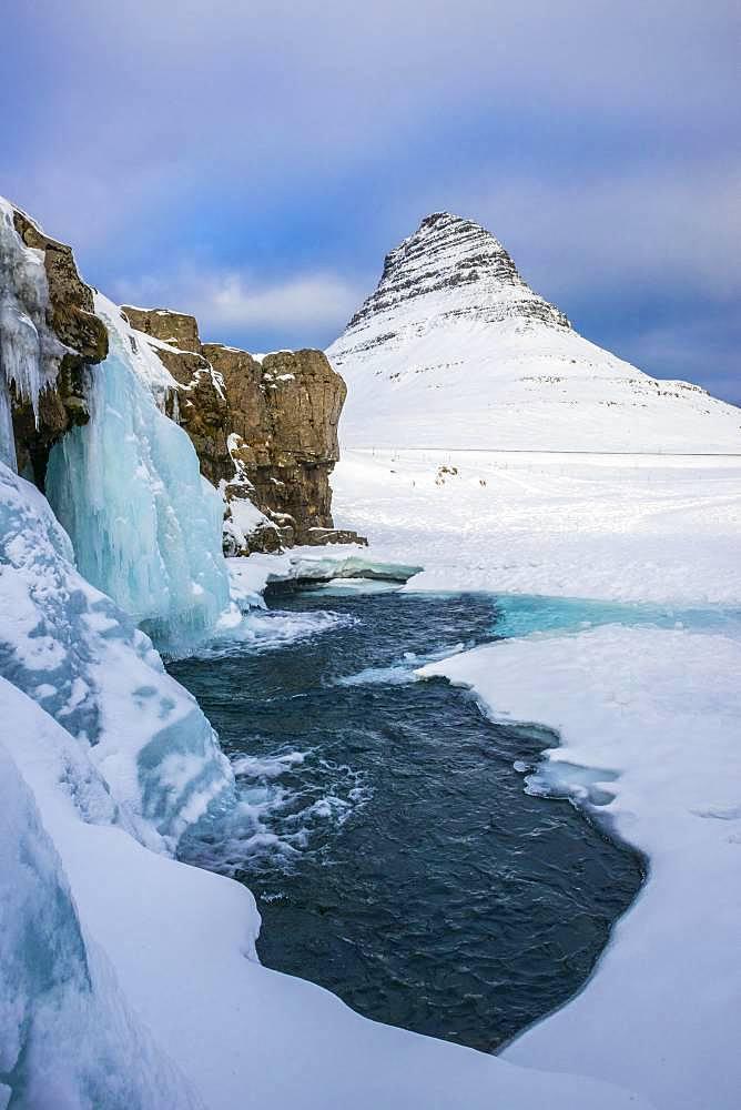Frozen waterfall Kirkjufellsfoss and the mountain Kirkjufell with snow, peninsula Snaefellsnes, Vesturland, Iceland, Europe