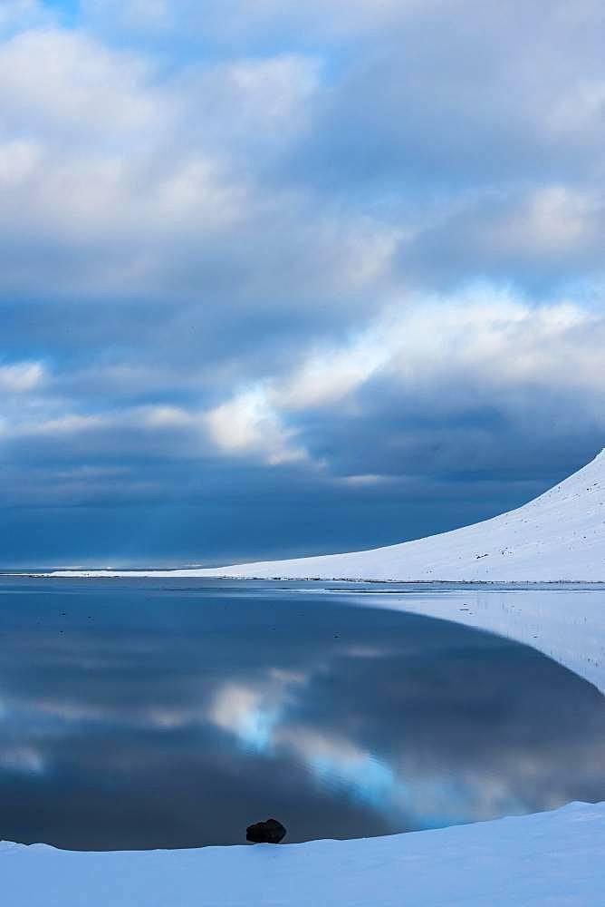 Snow-covered coastal landscape with water reflection, north coast of the peninsula Snaefellsnes, Grundarfjoerdur, Iceland, Europe