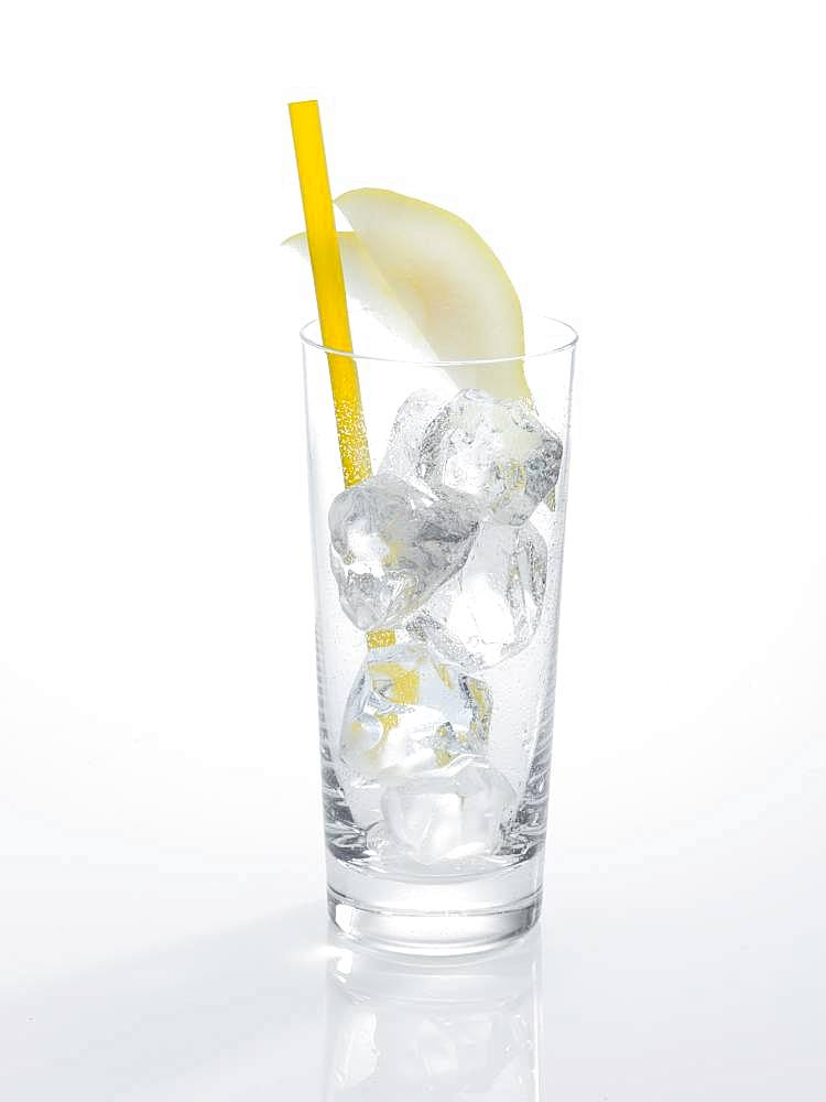 Glass prepared for cocktails, decorated with pear slice cubes, drinking straw, ice cubes, Germany, Europe