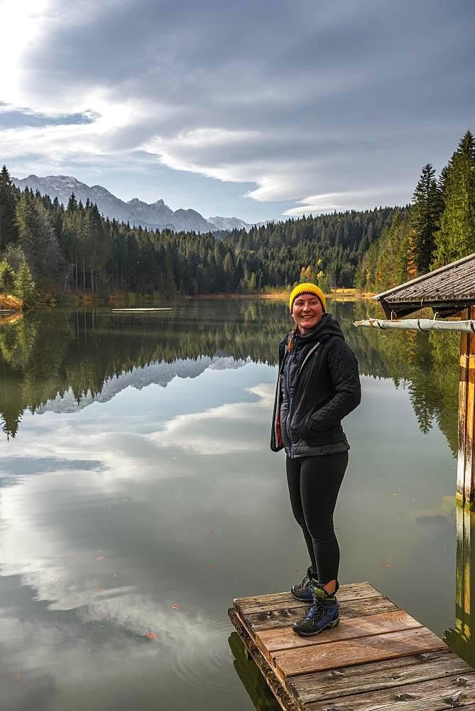 Young female hiker standing on a footbridge at Grubsee, near Kruen, Karwendel, Upper Bavaria, Bavaria, Germany, Europe