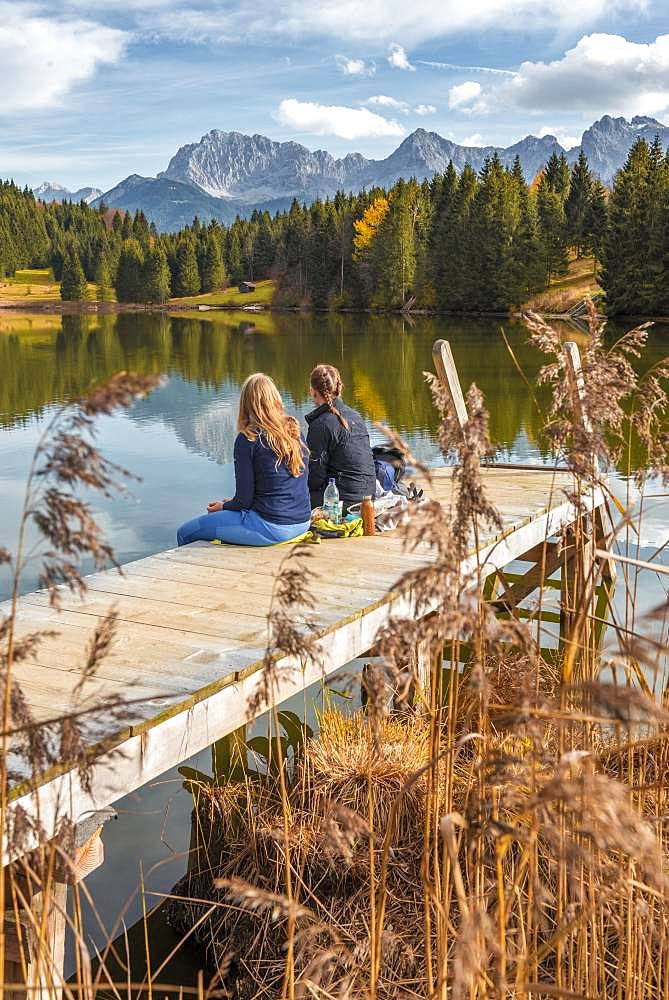 Two young women sitting at a jetty having a snack, Lake Geroldsee, Mittenwald, Karwendel, Bavaria, Germany, Europe