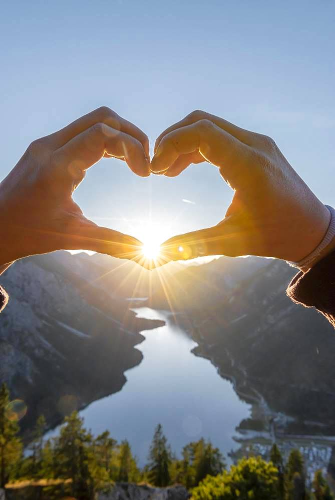 Hand forms a heart in front of alps and mountain lake, sun star, symbol love for nature and hiking, view from Schoenjoechl, Plansee, Tyrol, Austria, Europe