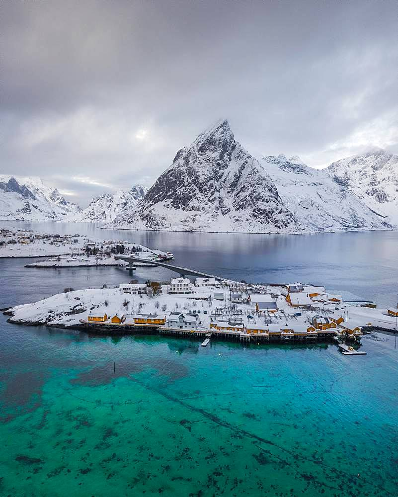 Belbe stilt houses at turquoise sea in winter, Sakrisoy, drone shot, Lofoten, Norway, Europe