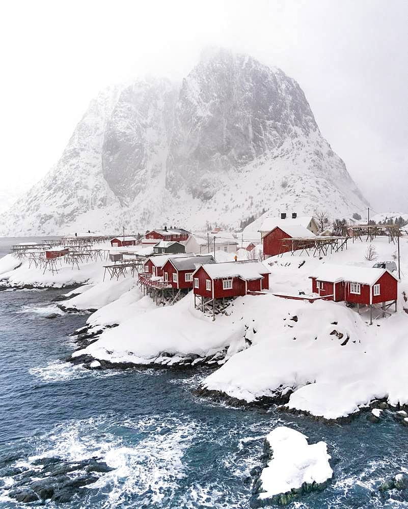 Snowstorm, red stilt houses, Hamnoy, drone shot, Lofoten, Norway, Europe