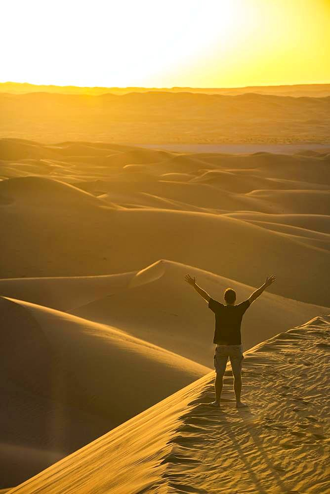 Man enjoying the sunset in the giant sanddunes of the Sahara, Timimoun, Algeria, Africa