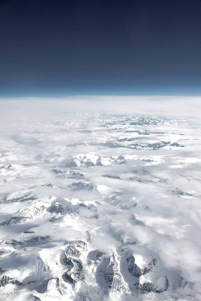 View from the plane to snow-covered mountainous landscape, horizon, bird's eye view, Greenland, North America