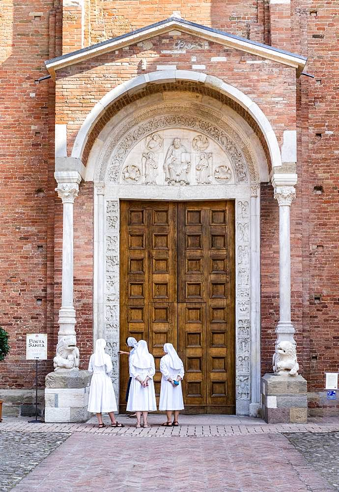 Nuns contemplate the Porta Santa of the Abbey Church of San Silvestro, Romanesque, Nonantola, Province of Modena, Emilia-Romagna, Italy, Europe