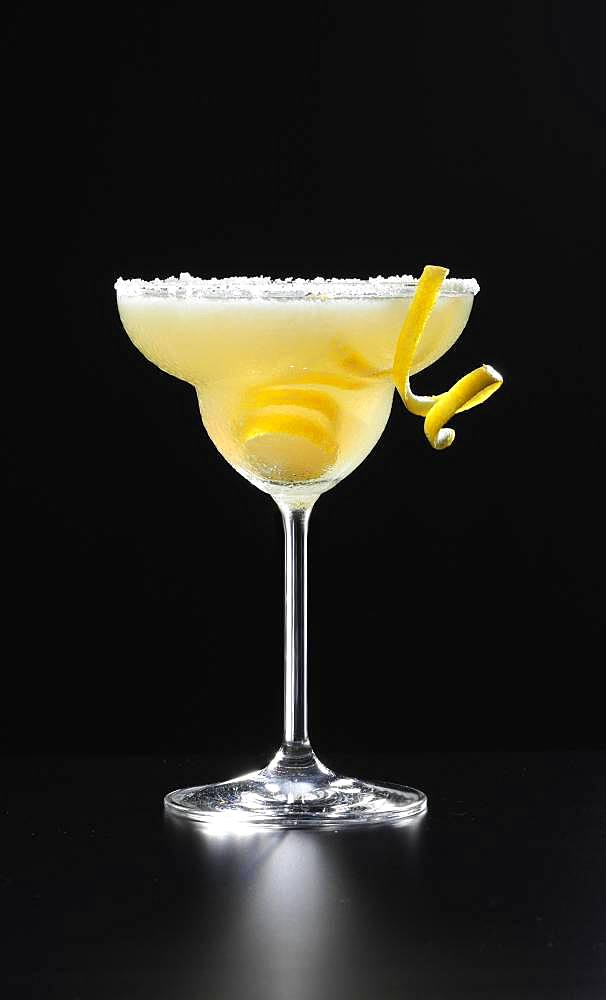 Cocktail with lemon peel, black background, Germany, Europe