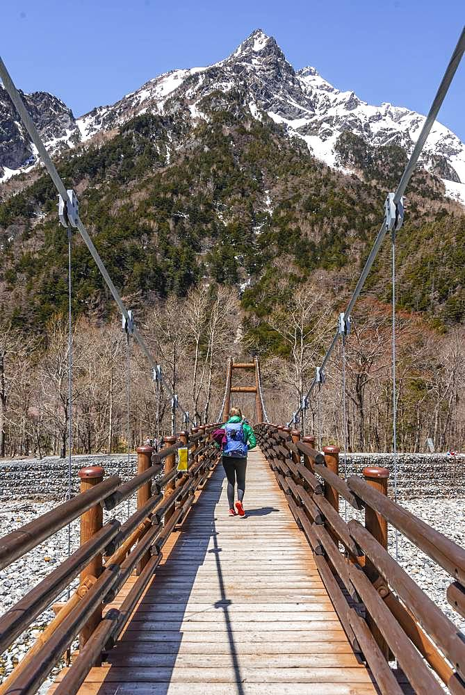 Woman walking over Myojin Bridge, Japanese Alps, Kamikochi, Matsumoto, Nagano, Japan, Asia
