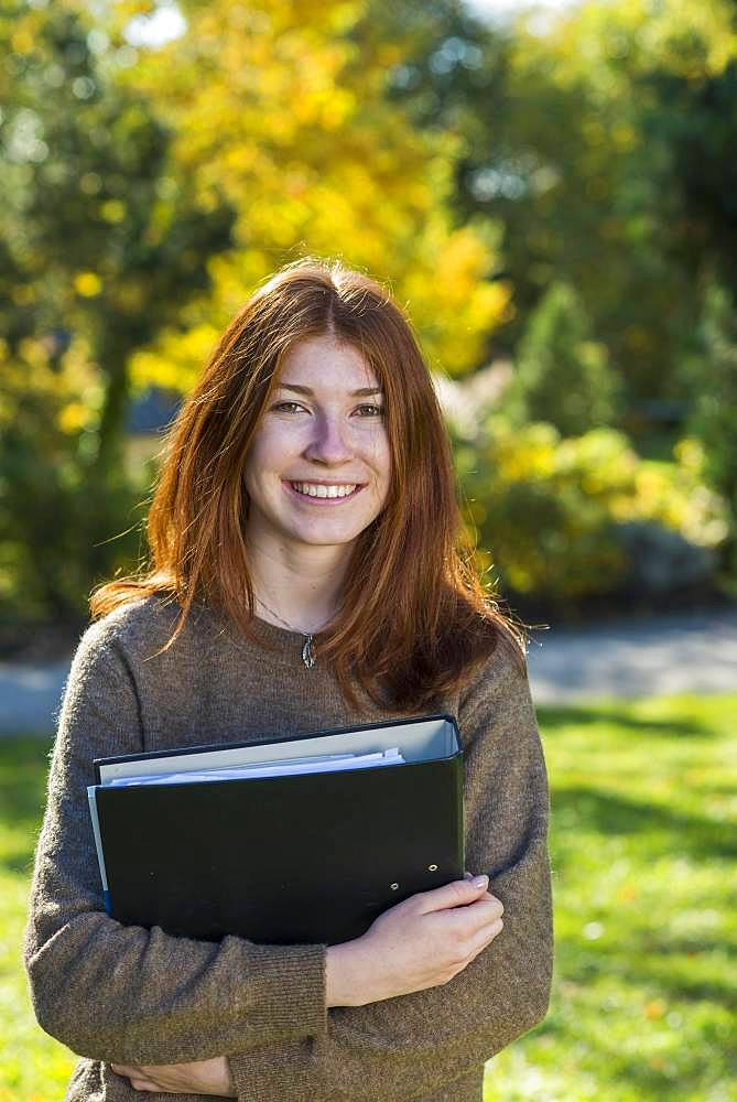 Young smiling red-haired woman, student, pupil holds folder, Bavaria, Germany, Europe