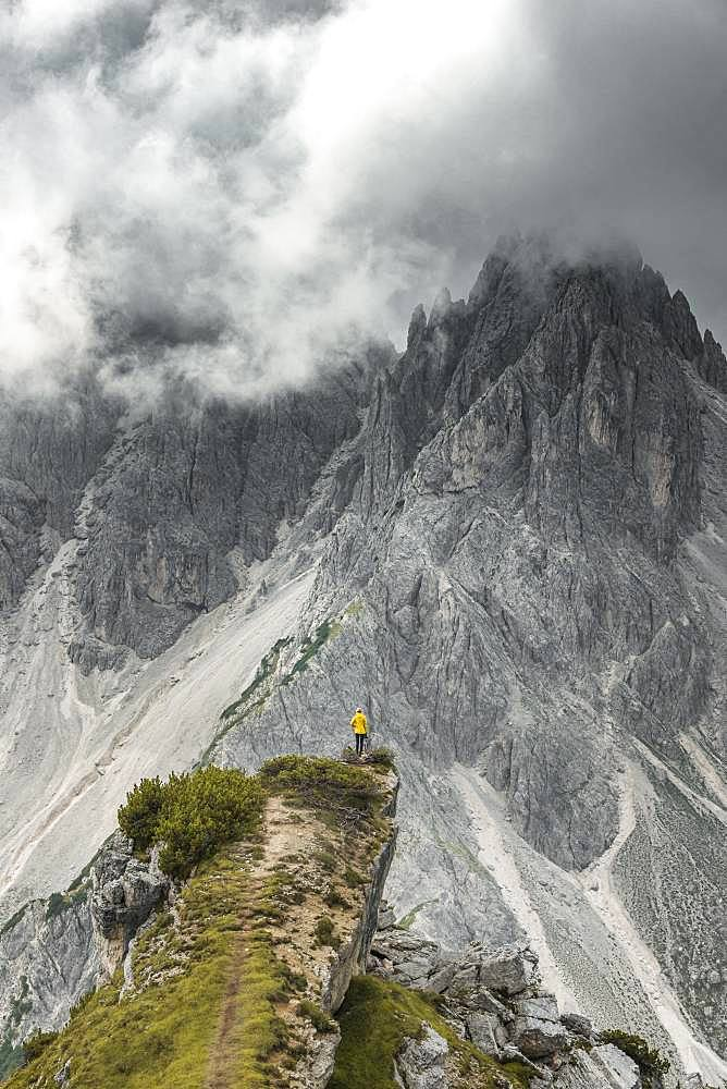 Woman in yellow jacket standing on a ridge, behind her mountain peaks and sharp rocky peaks, dramatic clouds, Cimon the Croda Liscia and Cadini group, Auronzo di Cadore, Belluno, Italy, Europe