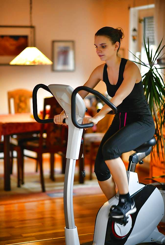 Young woman doing sports at home on an ergometer, Stuttgart, Baden-Wuerttemberg, Germany, Europe