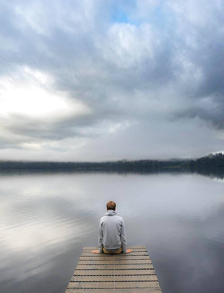Young man sitting on a jetty looking over a lake, foggy atmosphere, Lake Mapourika, West Coast, South Island, New Zealand, Oceania
