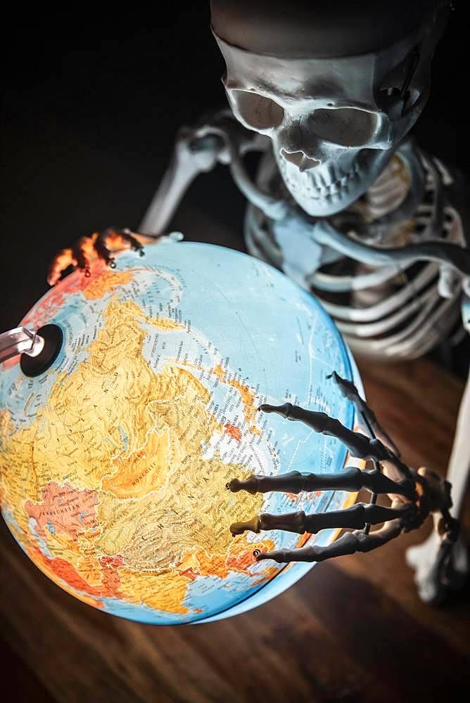 Skeleton with bony hand on globe, symbolic image of war and environmental catastrophe, Germany, Europe
