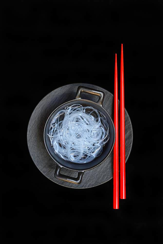 Asian glass noodles in pot and red chopsticks, Germany, Europe
