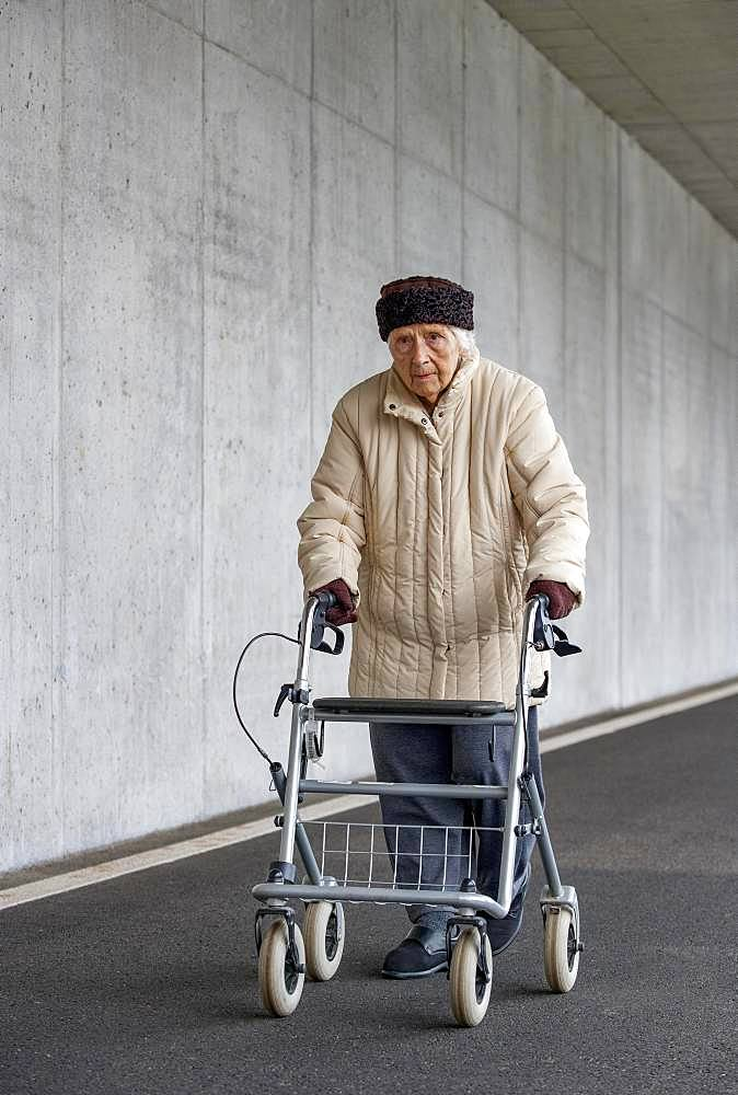 Senior citizen with walker walks in an underpass, Austria, Europe
