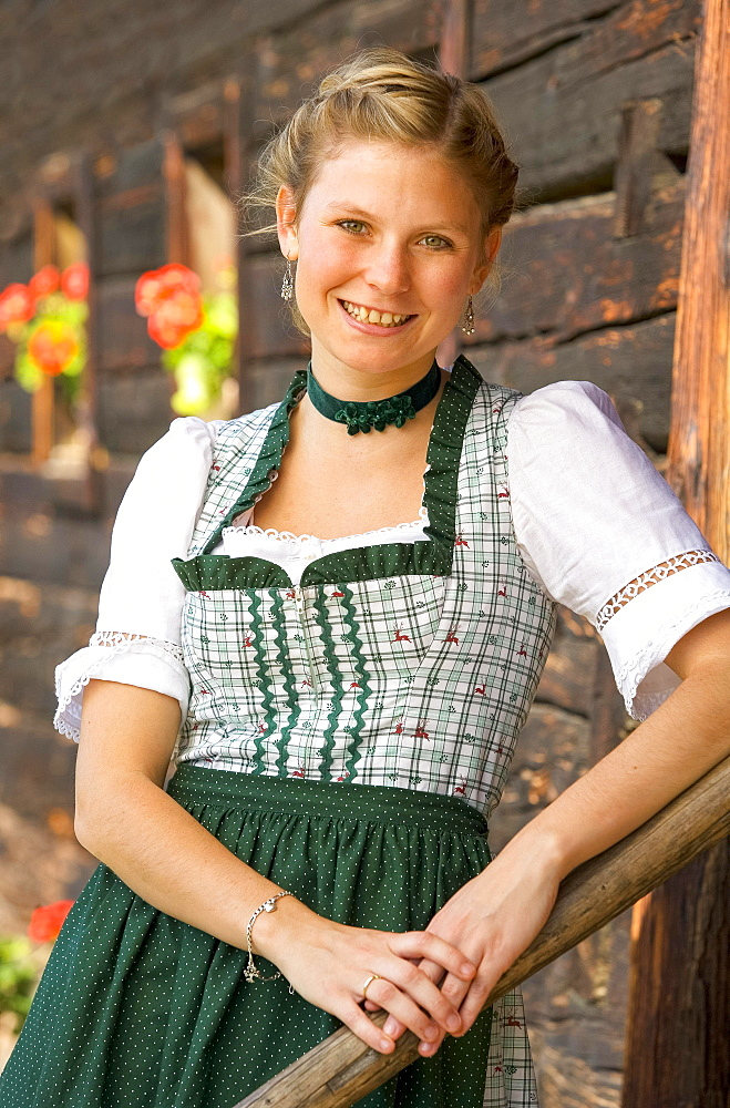 Young woman in dirndl standing in front of an old farmhouse, 19 years old, Upper Austria, Austria, Europe